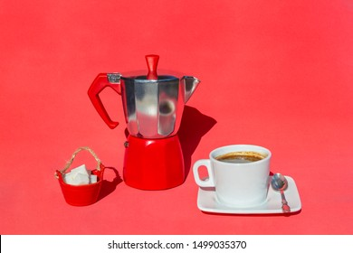 Italian coffee maker, moka pot coffee, cup and saucer of hot drink , sugar on red background, copy space