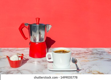 Italian coffee maker, moka pot coffee, cup and saucer of hot drink , sugar on marble table with red background, copy space