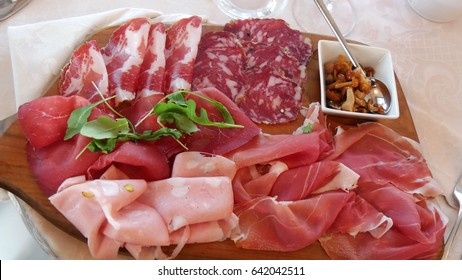 italian cold cuts on a wooden board: salumi,  bresaola and rocket salad, bacon, mortadella and raw ham.  and some mushrooms in oil.