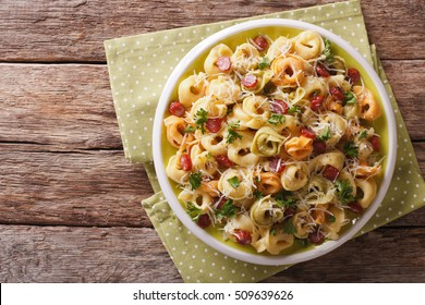 Italian colored tortellini with parmesan and sliced sausages close-up on a plate. horizontal view from above