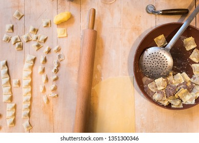 Italian cooked agnolotti with stew ragù in a soup plate and uncooked agnolotti with rolling pin and pasta cutting wheel on a wooden cutting board