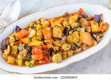 Italian cuisine - caponata on a plate on a rustic background