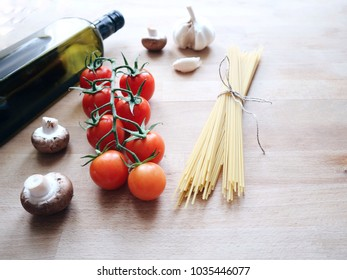 Italian cuisine concept. Pasta spaghetti, fresh cherry tomatoes, button champignons, olive oil, garlic. Healthy simple eating. Traditional food on a wooden background.