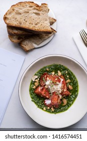Italian cuisine dish, burrata with fresh red tomatoes in green pesto sauce, olive oil and cashew nuts. All in white bowl with golden cutlery and pieces of black toasted bread. Lunchtime snack in cafe.
