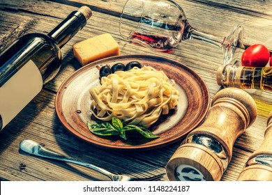 Italian cuisine. Fettuccine pasta with parmesan cheese, basil and cream sauce on wooden background, glass of red wine Ingredients on table, close up