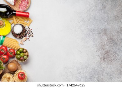 Italian cuisine food ingredients. Pasta, cheese, salami, olives and wine. Top view flat lay on stone table with copy space