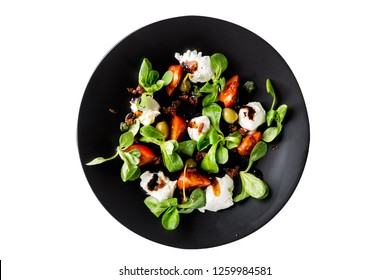 Italian cuisine. Fresh italian caprese salad with mozzarella and tomatoes on dark plate isolated on white background. Top view.