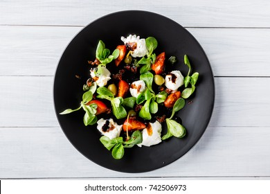 Italian cuisine. Fresh italian caprese salad with mozzarella and tomatoes on dark plate on white wooden table. Top view