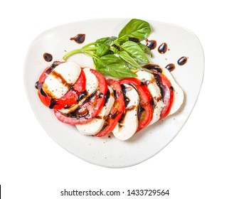 italian cuisine insalata caprese (caprese salad) - top view of sliced mozzarella cheese and tomato with basil twig seasoned by olive oil and balsamic vinegar on plate isolated on white background
