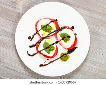 italian cuisine insalata caprese (caprese salad) - top view of stacks from sliced mozzarella cheese, tomato, basil leaf seasoned by olive oil, balsamic vinegar and pesto sauce on plate on wooden table