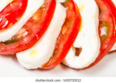 italian cuisine insalata caprese (caprese salad) - sliced mozzarella cheese and tomato close up