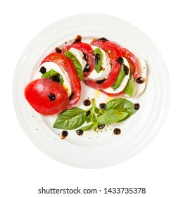 italian cuisine insalata caprese (caprese salad) - top view of sliced mozzarella cheese and tomato with basil leaves seasoned by olive oil and balsamic vinegar on plate isolated on white background