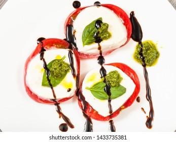 italian cuisine insalata caprese (caprese salad) - top view of stacks from sliced mozzarella cheese, tomato, basil leaf seasoned by olive oil, balsamic vinegar and pesto sauce on white plate