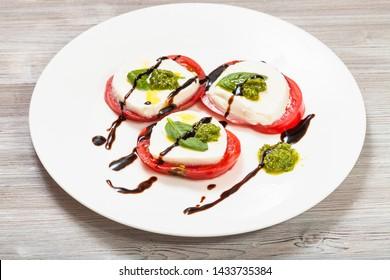 italian cuisine insalata caprese (caprese salad) - stacks from sliced mozzarella cheese, tomato, basil leaf seasoned by olive oil, balsamic vinegar and pesto sauce on white plate on wooden table