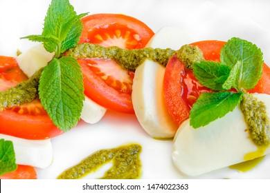 italian cuisine insalata caprese salad sliced mozzarella cheese and tomato close up. Caprese salad recipe concept, top view