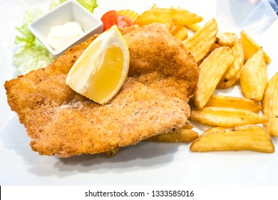 Italian cuisine - Pollo alla Milanese (pan-fried breaded Chicken Milanese schnitzel) with roasted potatoes and lemon close up on white plate in local restaurant in Lombardy