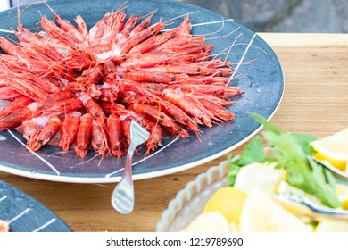 Italian cuisine with raw seafood appetizer and red prawns served in a blue plate during a lunch in a farm in Puglia, Italy.