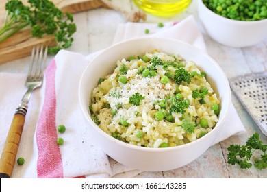 Cuisine italienne. Risi e bisi, cuisine vénitienne.  Plaque de risotto au pois vert avec pois vert, fromage parmesan grillé, huile d'olive et persil sur fond clair