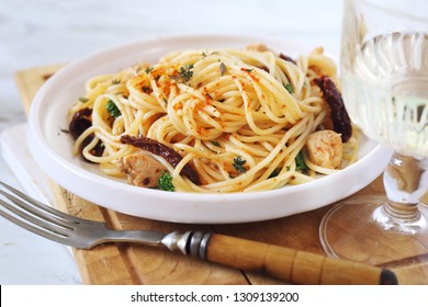 Italian cuisine. Spaghetti with dried tomatoes, garlic grilled chicken and glass of white wine. Focus selective