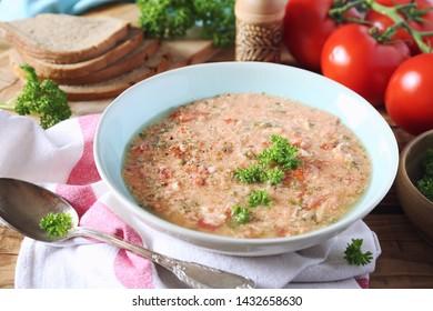 Italian cuisine. Stracciatella tomato soup: parsley, eggs and parmesan cheese on dark background