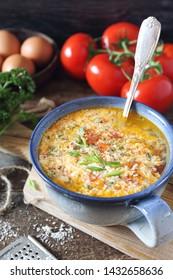 Italian cuisine. Stracciatella tomato soup: parsley, eggs and parmesan cheese