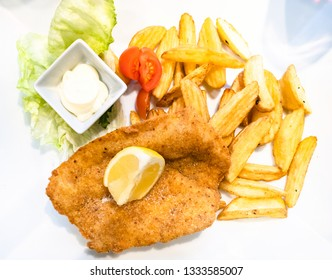 Italian cuisine - top view of Pollo alla Milanese (pan-fried breaded Chicken Milanese schnitzel) with roasted potatoes and lemon close up on white plate in local restaurant in Lombardy