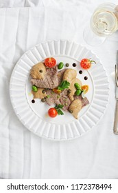 Italian cuisine- Vitello tonnato sliced veal with tuna sauce, capers, olive served on white plate  . Top view, copy space.