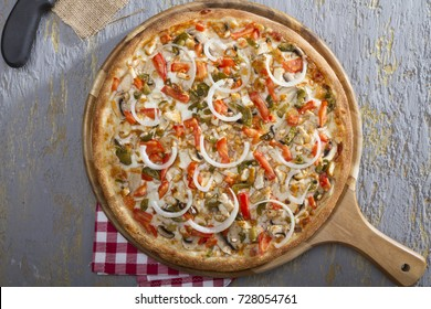 Italian Delicious Fresh Hot Mix Baked Chicken Pizza with Melting Cheese, hot spicy jalapeno pepper, sliced white onion, mushroom, cube cut tomato and ham serving on grey textured rustic background.