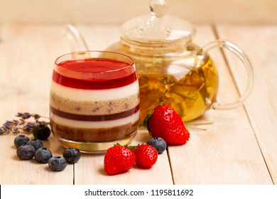 Italian dessert - panna cotta with berries and herbal lavender tea. Homemade berries aspic with different layers of chocolate, milk, cream, berry with fresh strawberries and blueberries