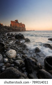 Italian destination: Acicastello in Sicily at sunset against a clear blue sky. Photo taken by the beach; waves on foreground.