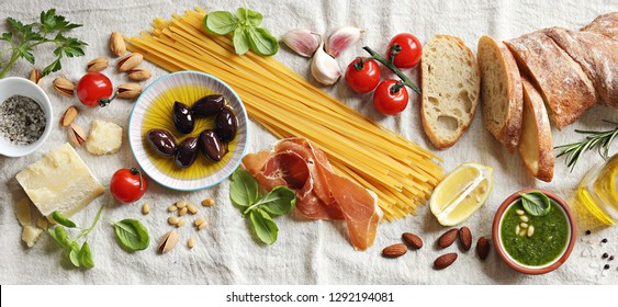Italian dinner table concept with spaghetti,vegetables, bread olives and herbs. Ingredients for cooking of traditional mediterranean dinner or lunch. Overhead view