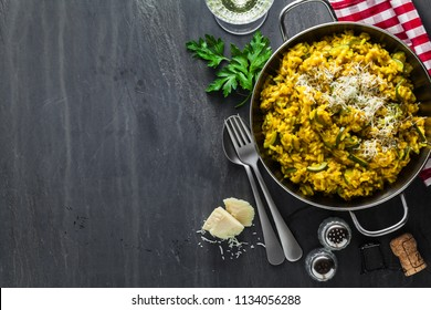 Italian dish yellow Risotto milanese with saffron, zucchini and Parmesan cheese on a black slate table with white wine in a glass. north Italy kitchen. copy space