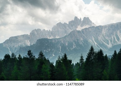 Italian Dolomites landscape. Light after rain in Dolomites. Rocky peaks in the background surrounded by rain clouds. Layers of forest and mountains ridge. Rocky Mountains Dolomiti. Storm rain