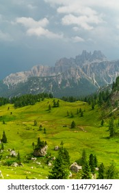 Italian Dolomites Landscape. Light after rain in Dolomites. Rocky peaks in the background surrounded by rain clouds. Mountain valley with layers of forest and mountains. Beautiful light in Alps. Italy