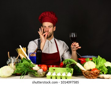 Italian drink and sommelier concept. Man in hat and apron shows Perfect Taste sign. Chef with satisfied face holds glass of wine on black background. Cook works in kitchen near vegetables and tools.