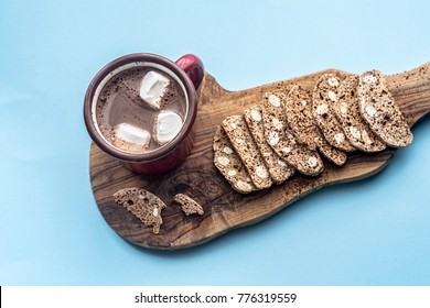 Italian dry cookies cantucci or biscotti with nuts and hot chocolate on a wooden table. A bunch of homemade cookies. Top view
