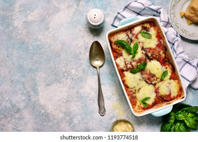 Italian eggplant dish melanzane alla parmigiana on a light blue slate, stone or concrete background.Top view with copy space.