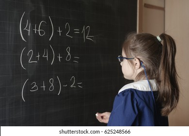 Italian elementary school girl (first-grader) solve mathematics examples. The student thinks and feels near the Board. Mathematical tasks.