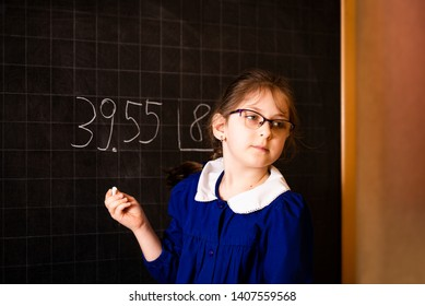 Italian elementary school girl trying to make a long division at the blackboard. The student looking for help. Mathematical tasks.