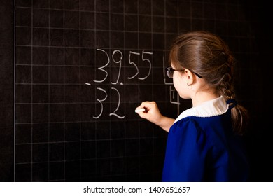 Italian elementary school girl trying to make a long division at the blackboard. Mathematical tasks.