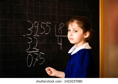 Italian elementary school girl trying to make a long division. The student thinks and feels near the blackboard. Mathematical tasks.
