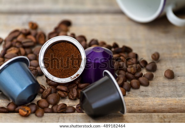 Capsule di caffè espresso italiano o cialde su fondo legno con alcuni chicchi di caffè tostati