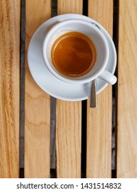 Italian espresso coffee cup top view on wooden stripes table background, space for text