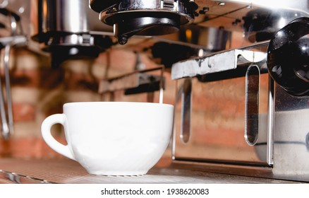 Italian espresso machine on a restaurant counter offering freshly brewed coffee in a small cup