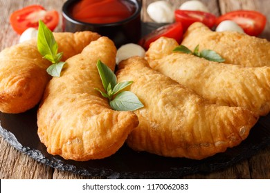 Italian fast food: fried panzerotti with tomato sauce, herbs and mozzarella close-up on a black board. horizontal, rustic