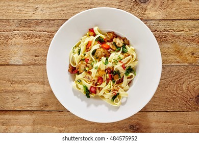 Italian fettuccine or tagliatelli pasta with mushrooms, tomato and fresh basil for an energising carbohydrate meal viewed from overhead on wood