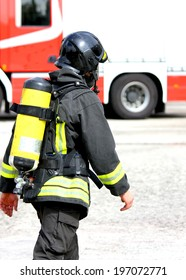 Italian firefighter with the oxygen cylinder and the helmet walks towards the fire