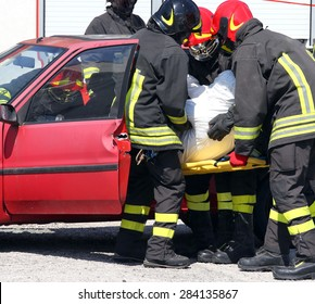 italian firemen in action and pull the injured from the car after the accident
