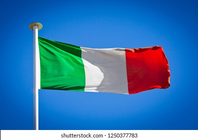 Italian flag blowing in strong wind against pure blue sky. Tricolour, symbol of national patriotism.