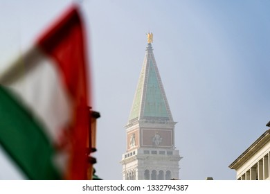 Italian flag in front of St Mark's Campanile (Campanile di San Marco) in the Piazza San Marco, Venice, Italy. Selective focus on  San Marco bell tower.